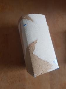 Tetrapack, von dem die bunte Folie teilweise abgezogen wurde