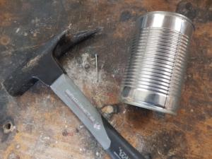 Hammer, Nagel und leere Dose auf einer Werkbank