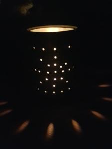 Eine Kerze scheint durch eine Dose mit Löchern.