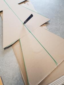 Die Pappkartons werden für das Zusammenstecken in der Mitte bis zur Hälfte auseinander geschnitten.
