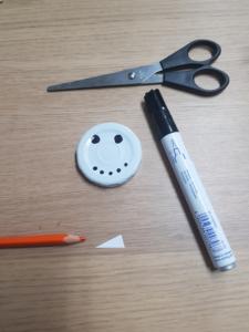 Weißer Denkel mit schwarzen Punkten für Nase und Mund, außerdem ein Papier-Dreieck, das noch orange bemalt wird für die Karotten-Nase.