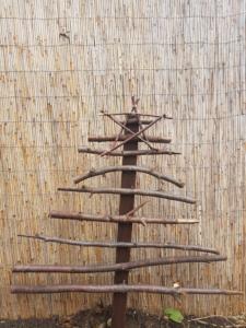 Baum aus Ästen und Holz zusammen gehämmert mit einem Ast-Stern an der Spitze