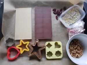 Vorbereitung zum Schokolade machen: weiße und dunkle Schokolade, Plätzchen-Formen, Pralinen-Formen, getrocknete Cranberries, bunte Zuckerperlen und gehackte Walnüsse auf einem Tablet mit Backpapier