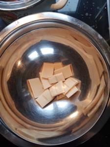 Die helle Schokolade wurde in Stücke gebrochen und in eine Schüssel gefüllt. Die Schüssel steht in einem Topf mit Wasser auf dem Herd.