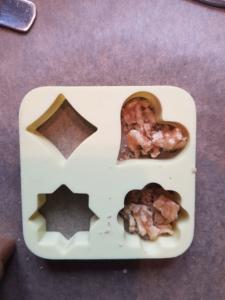 Gehackte Walnüsse wurden in Pralinen-Formen gefüllt.