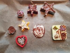 Die geschmolzene Schokolade wurde in die Formen gefüllt. Manche wurden mit Zuckerstreuseln verziert. In der Mitte liegt ein Stück Schokolade ohne Form: Sie wurde mit einem Löffel auf das Backpapier gestrichen.