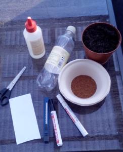 Was du für den Kresseigel brauchst: PET-Flasche, Erde, Kressesamen, Edding, Teppichmesser, Papier, Schere, Kleber