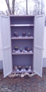 Die Türen des Schranks sind geöffnet. Im Schrank stehen mehrere Pflanz-Sets.