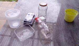 Verschiedene Gegenstände stehe auf einem Tisch:ein leeres Schraubgla, ein durchsichtiger Plastikeimer mit Deckel, eine leere Saftflasche aus Plastik, ene leere Sushi-Box,eine durchsichtige Plastik-Schale und ein Blumentopf