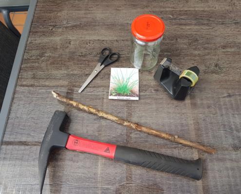 Was du für dein Pflanz·schild brauchst: Hammer, Ast, Schere, Bild von der Pflanze, Kleb·streifen und ein leeres Schraub·glas mit Deckel.