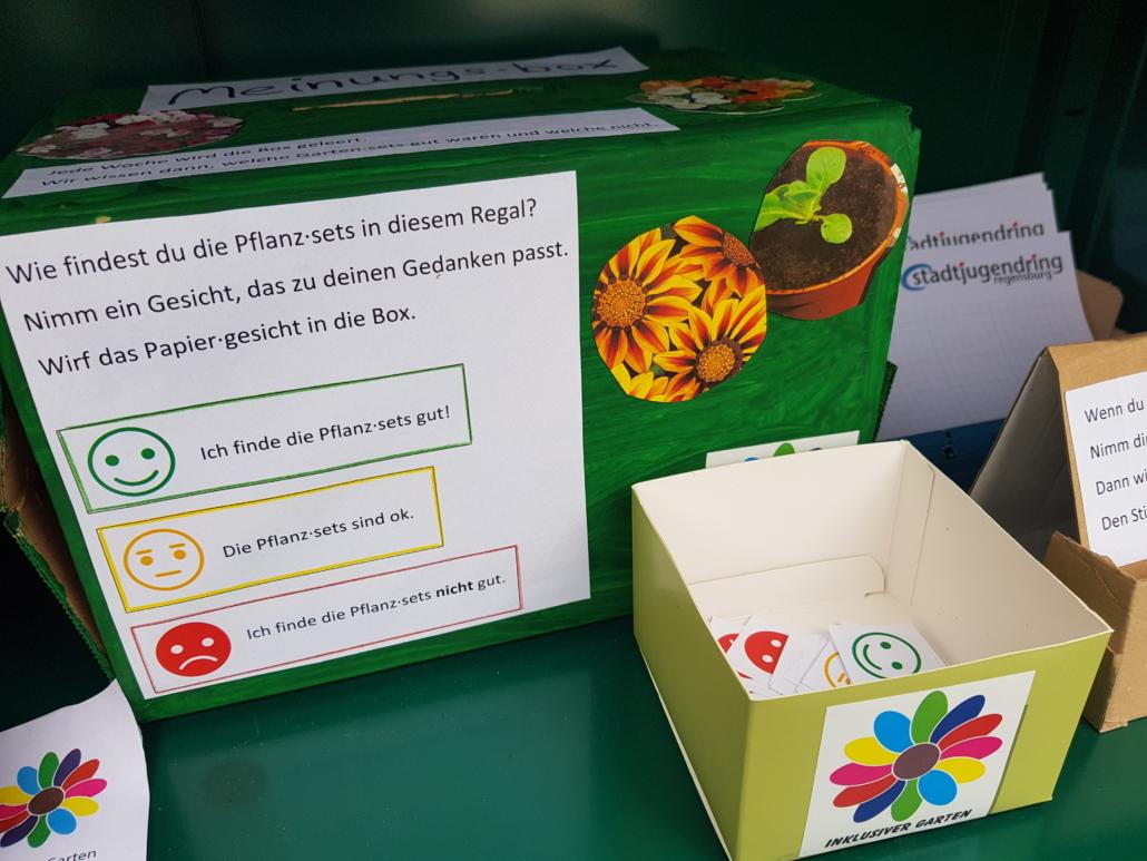 Unsere Meinungs·box in Grün. Davor steht eine kleine Schachtel mit Zetteln, auf denen verschiedene Gesichter sind.
