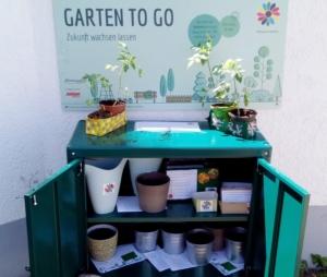 Foto des offenen Regals mit Töpfen, Gießkannen und Anleitung, darüber hängt das Schild für den Garten to go